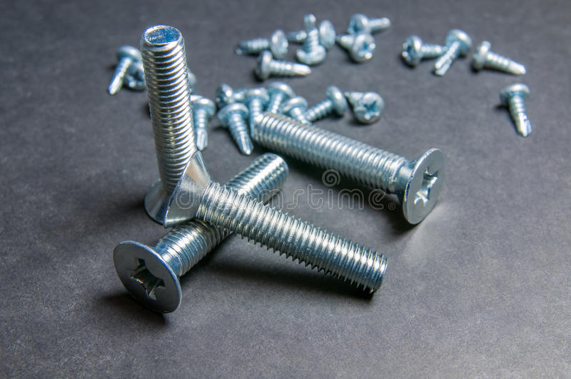 Bolts and Screws on grey. Left upright bolt (right light) royalty free stock image