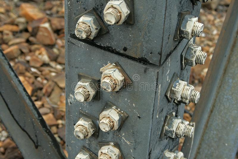 BOLTS IN STRUT OF ELECTRICAL PYLON. Large metal bolts and screws fastenings on support of robust electrical pylon stock photo