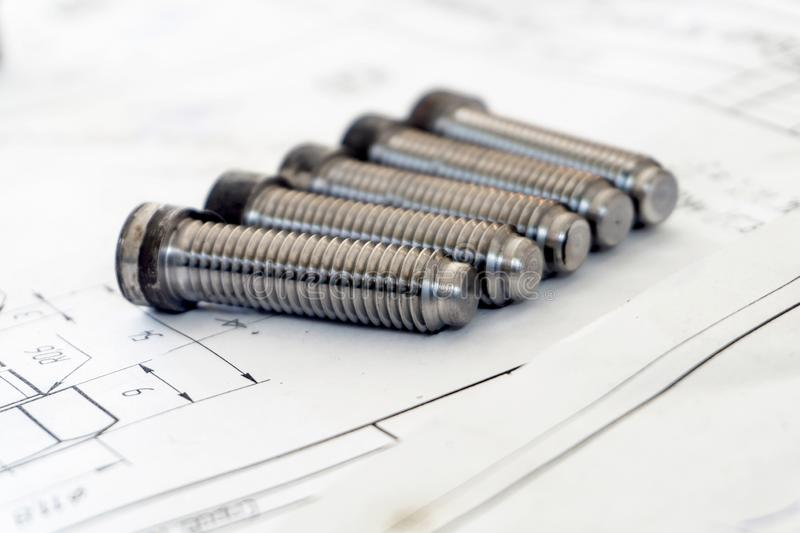Bolts after turning with thread on the background of technical drawings.  stock photo