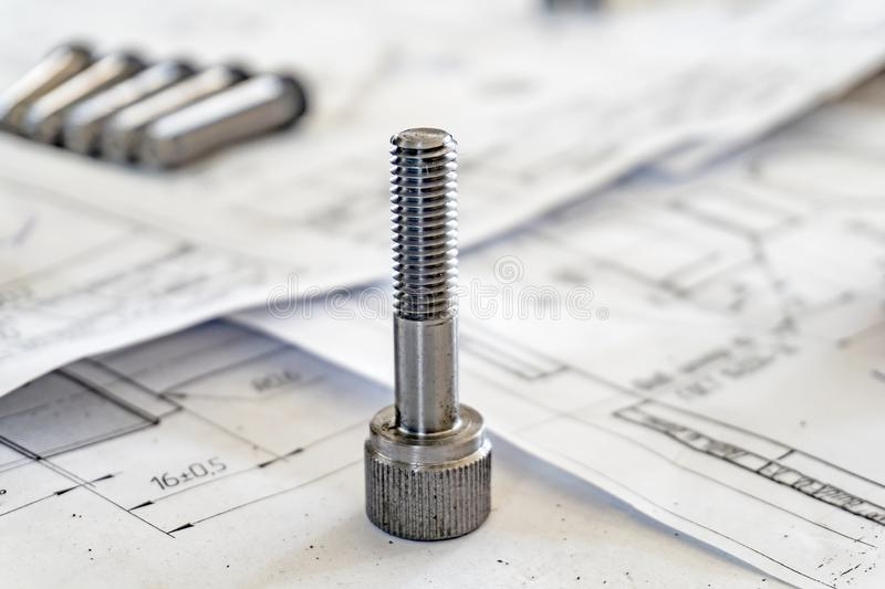 Bolts after turning with thread on the background of technical drawings.  stock photography