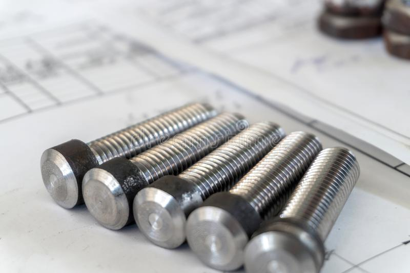 Bolts after turning with thread on the background of technical drawings.  royalty free stock photo