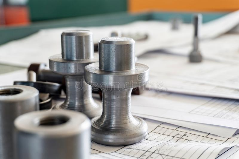 Bolts after turning with thread on the background of technical drawings.  royalty free stock image