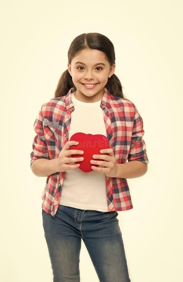 Bom cora??o Menina que guarda o cora??o vermelho Pouco crian?a que expressa o amor no dia de Valentim Menina bonito no amor tendo imagens de stock