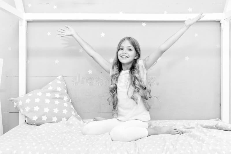 Bom dia Cabelo encaracolado longo da criança da menina acordado Despertar agradável A menina olha alegremente e completamente da  imagem de stock