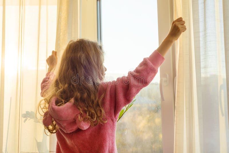 Bom dia A criança da menina nos pijamas abre cortinas e olhares para fora a janela fotografia de stock royalty free