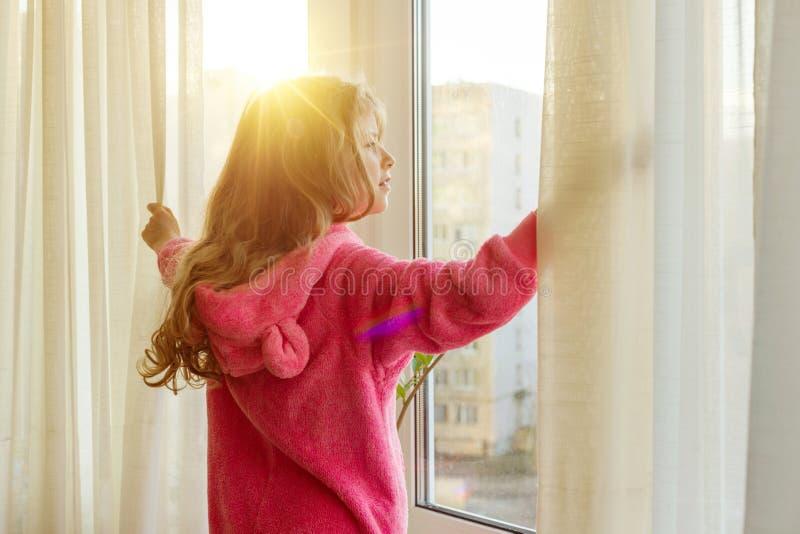 Bom dia A criança da menina nos pijamas abre cortinas e olhares para fora a janela fotografia de stock