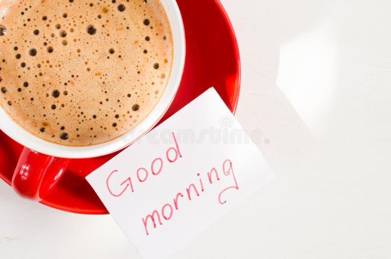 Bom dia da caneca e das notas do cappuccino na tabela rústica clara foto de stock