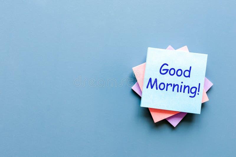 Bom dia - desejo por um bom dia Nota no fundo azul Com espaço vazio para o texto, o modelo e o molde imagens de stock