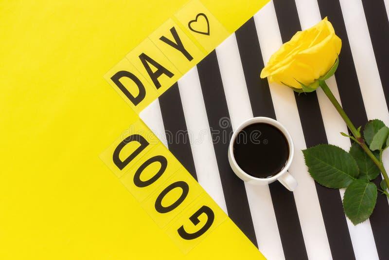 Bom dia do texto, café, e rosa amarela no guardanapo preto e branco à moda no fundo amarelo Opinião superior da configuração do p imagem de stock
