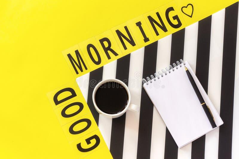Bom dia do texto, café, e rosa amarela no guardanapo preto e branco à moda no fundo amarelo Opinião superior da configuração do p foto de stock