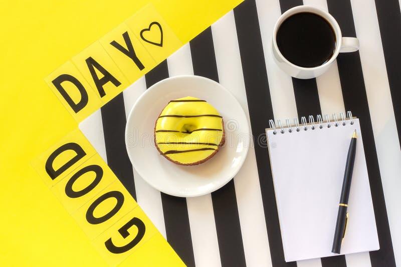 Bom dia do texto, caf?, e rosa amarela no guardanapo preto e branco ? moda no fundo amarelo Opini?o superior da configura??o do p foto de stock