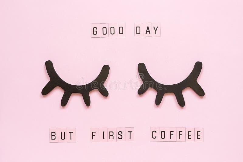 Bom dia do texto, mas primeiro café e pestanas pretas de madeira decorativas, olhos fechados, no fundo de papel cor-de-rosa paste fotografia de stock royalty free