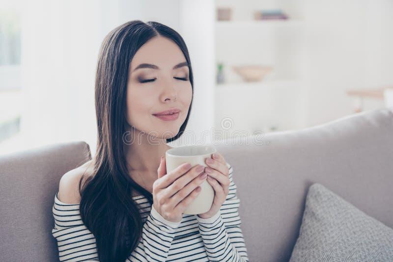 Bom dia! Feche acima do retrato da jovem senhora coreana sonhadora encantador que bebe o chá quente É relaxado, no vestuário desp imagem de stock royalty free