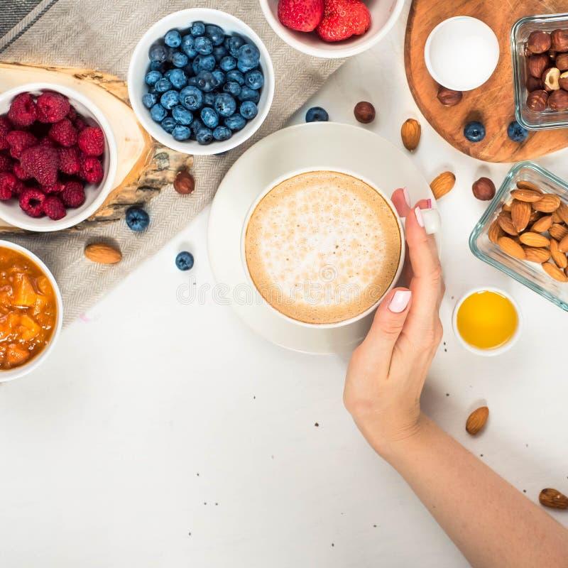Bom dia - fundo saudável do café da manhã com café da farinha de aveia, bagas, ovo, porcas Café, mãos, posse, copo Alimento de ma fotos de stock royalty free