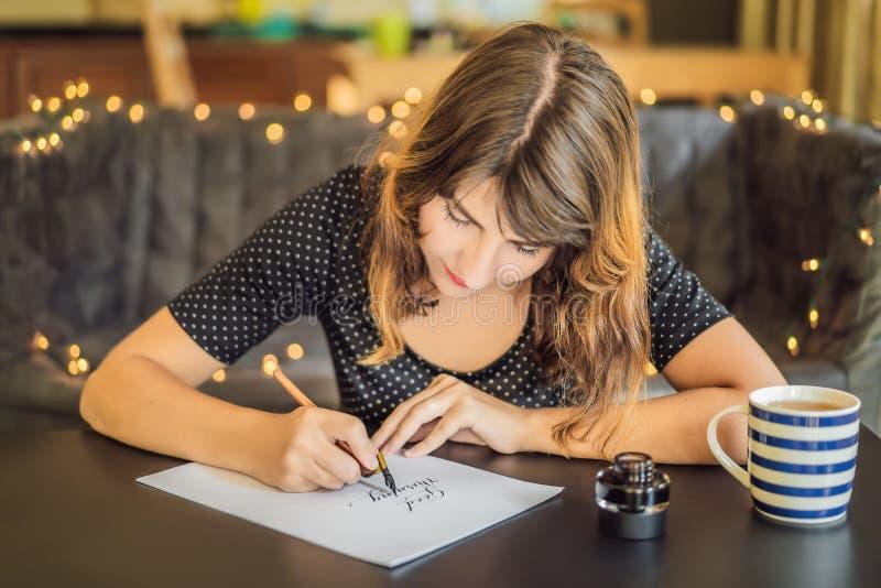 Bom dia O cal?grafo Young Woman escreve a frase no Livro Branco Inscreendo letras decoradas decorativas fotos de stock royalty free