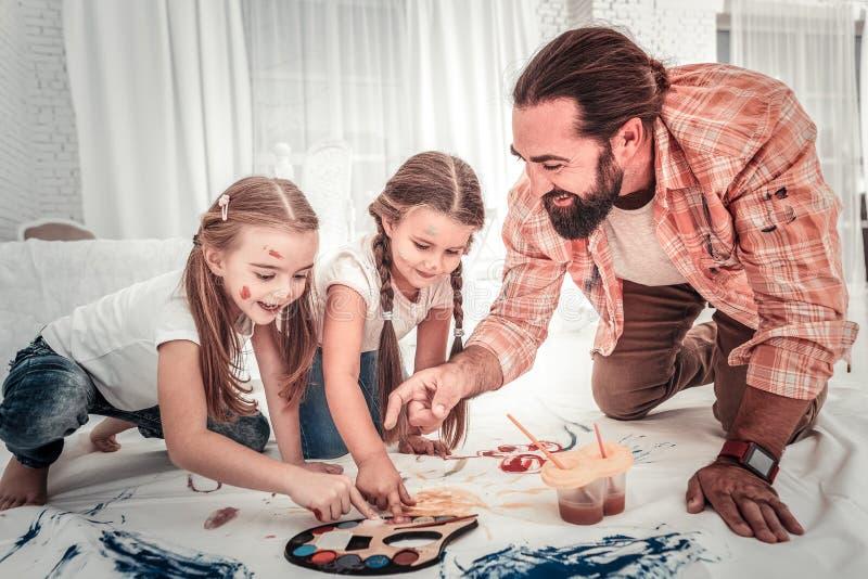 Bom pai novo que passa o tempo junto com sua pintura das crianças foto de stock