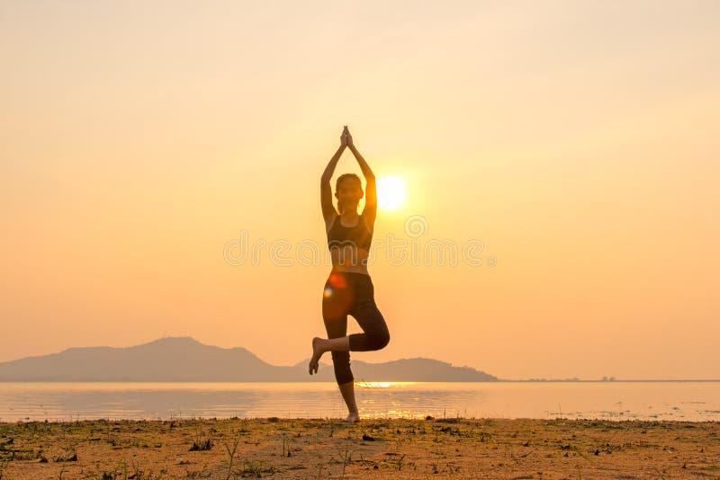 Bom saudável A silhueta da mulher do estilo de vida da ioga da meditação no por do sol do rio, relaxa vital imagens de stock royalty free