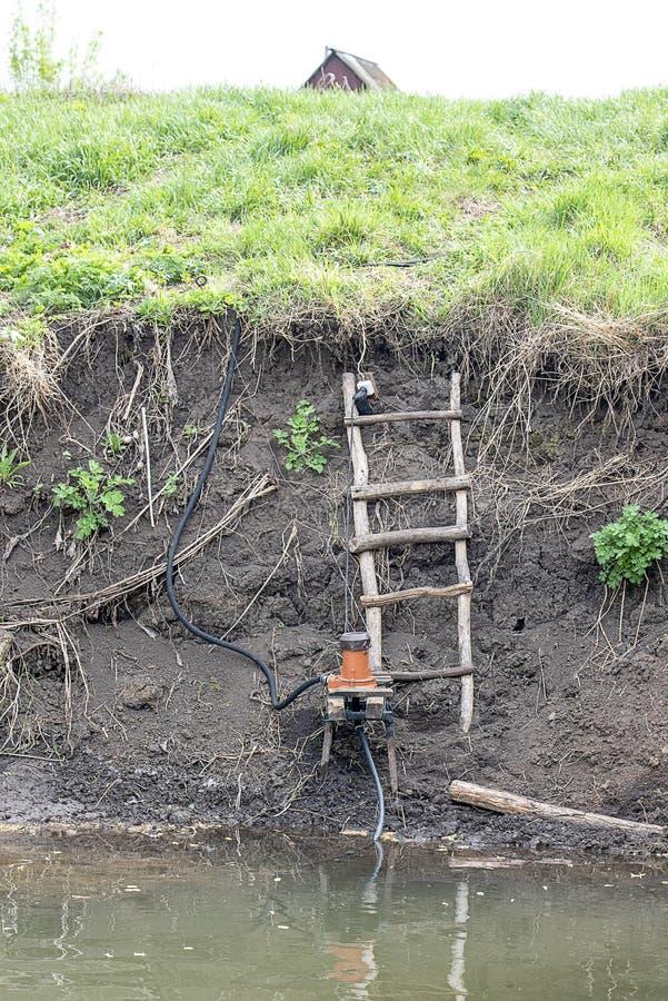 A bomba é instalada no banco do rio para a irrigação imagens de stock royalty free
