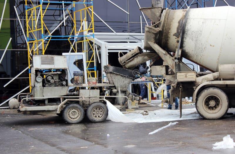 bomba concreta e misturador para trabalhar assoalhos junto de derramamento do cimento no shopping para o reparo fotos de stock