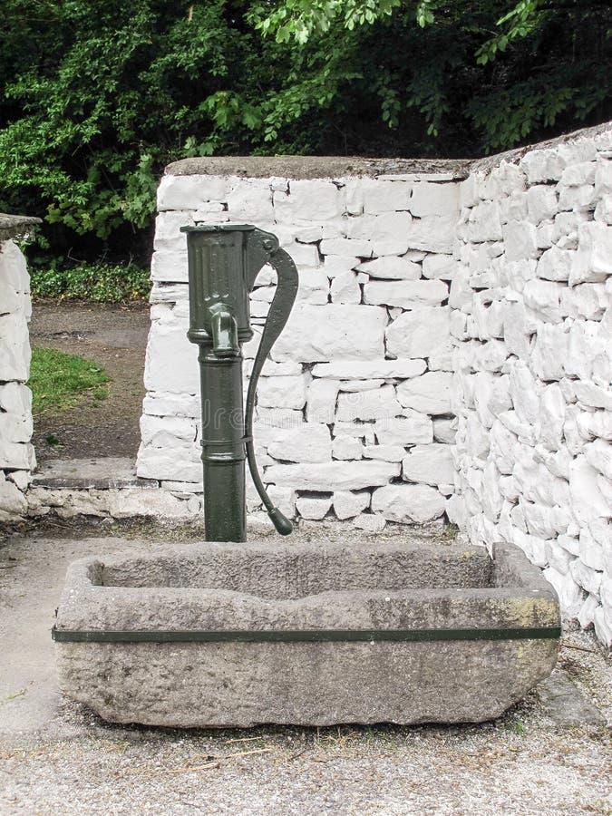 Bomba de água antiga com a calha de pedra da água foto de stock