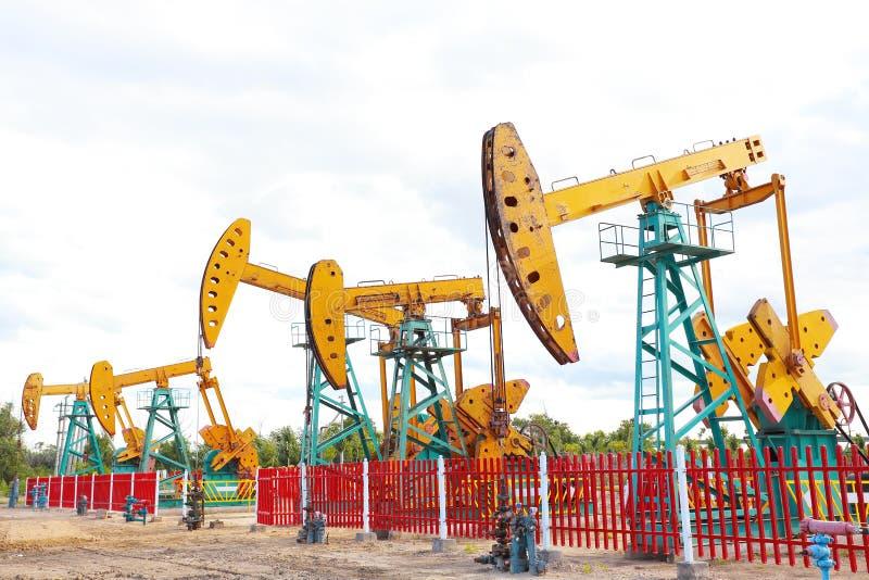Bomba de óleo amarela dourada do equipamento bruto do poço petrolífero imagem de stock