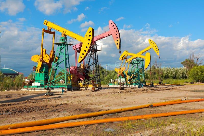 Bomba de óleo amarela e cor-de-rosa dourada do equipamento bruto do poço petrolífero fotografia de stock royalty free