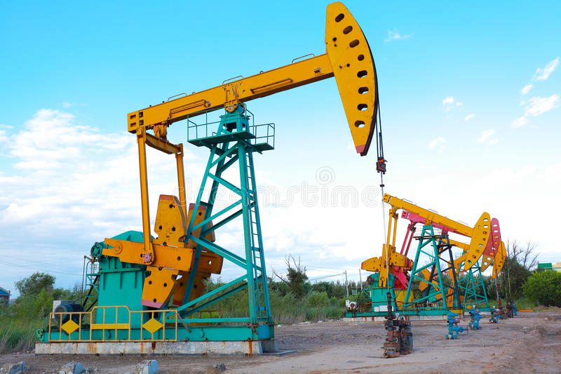 Bomba de óleo amarela e cor-de-rosa dourada do equipamento bruto do poço petrolífero foto de stock royalty free