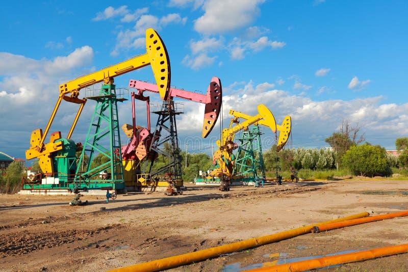 Bomba de óleo amarela e cor-de-rosa dourada do equipamento bruto do poço petrolífero foto de stock