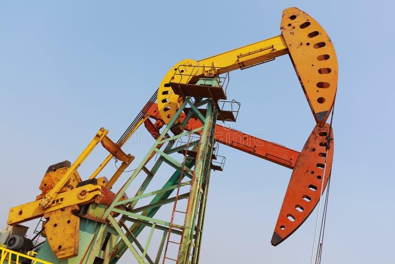 Bomba de óleo amarela e vermelha dourada do equipamento bruto do poço petrolífero fotos de stock royalty free