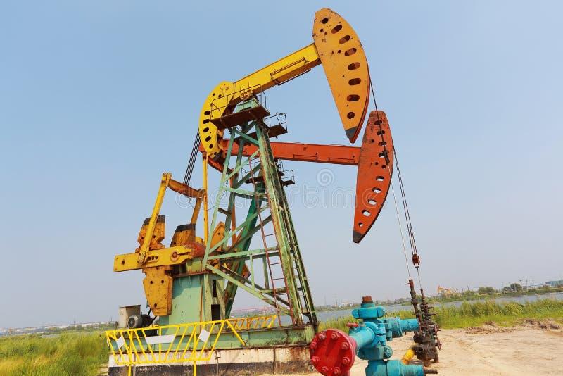 Bomba de óleo amarela e vermelha dourada do equipamento bruto do poço petrolífero imagem de stock royalty free