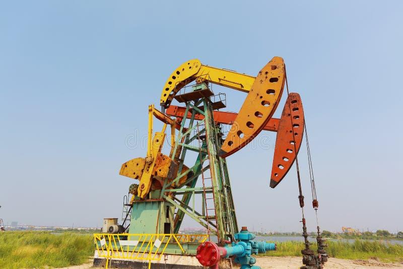 Bomba de óleo amarela e vermelha dourada do equipamento bruto do poço petrolífero imagem de stock