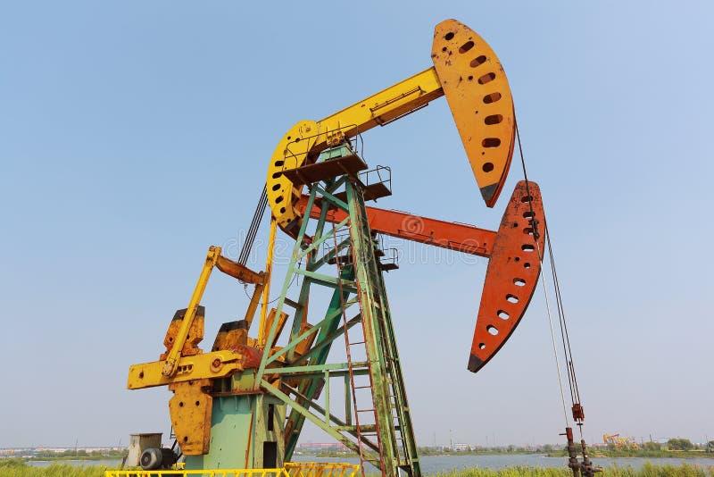 Bomba de óleo amarelo e alaranjado dourada do equipamento bruto do poço petrolífero fotografia de stock
