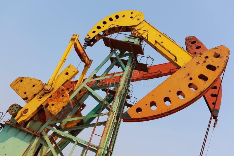 Bomba de óleo amarelo e alaranjado dourada do equipamento bruto do poço petrolífero foto de stock