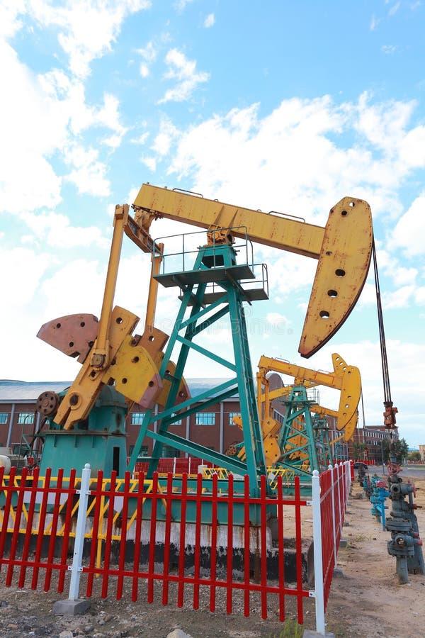 Bomba de óleo amarelo e alaranjado dourada do equipamento bruto do poço petrolífero fotos de stock royalty free
