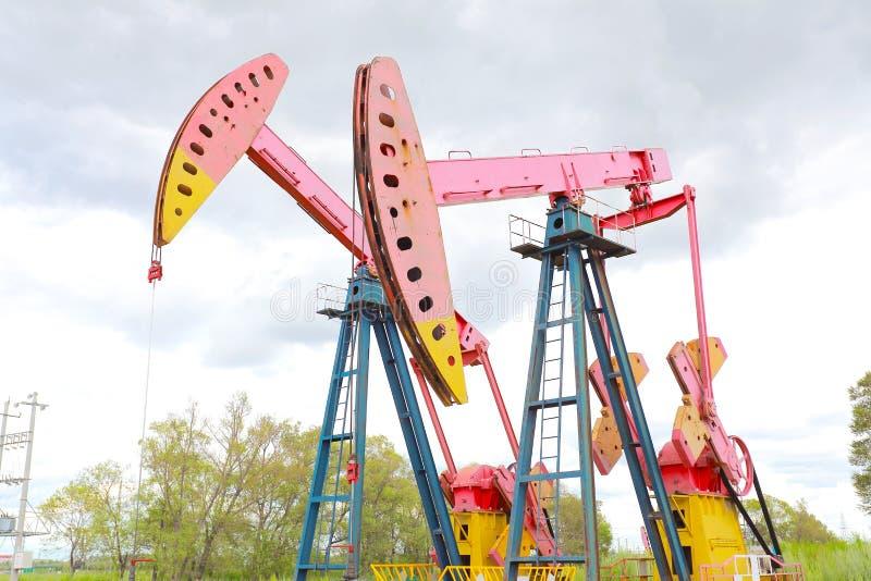 Bomba de óleo cor-de-rosa do equipamento bruto do poço petrolífero fotos de stock royalty free