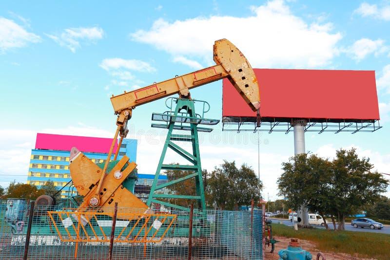 Bomba de óleo e quadro de avisos amarelos dourados do equipamento bruto do poço petrolífero foto de stock
