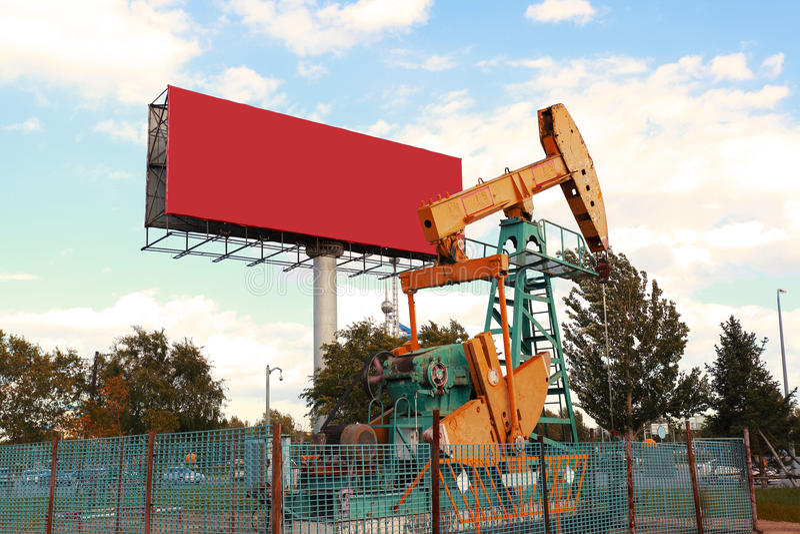 Bomba de óleo e quadro de avisos amarelos dourados do equipamento bruto do poço petrolífero fotografia de stock royalty free