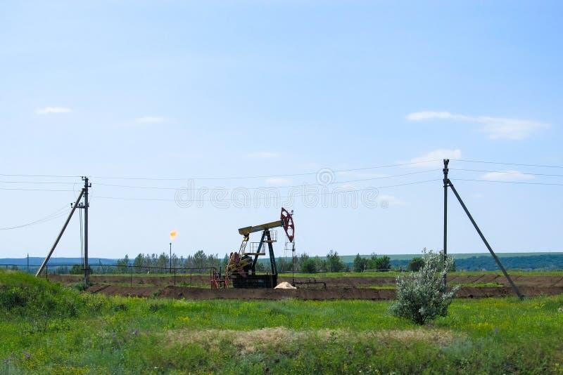 Bomba de óleo de trabalho na terra entre os campos verdes foto de stock