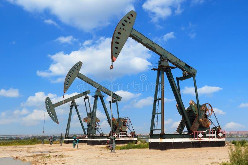 Bomba de óleo verde do equipamento bruto do poço petrolífero fotografia de stock