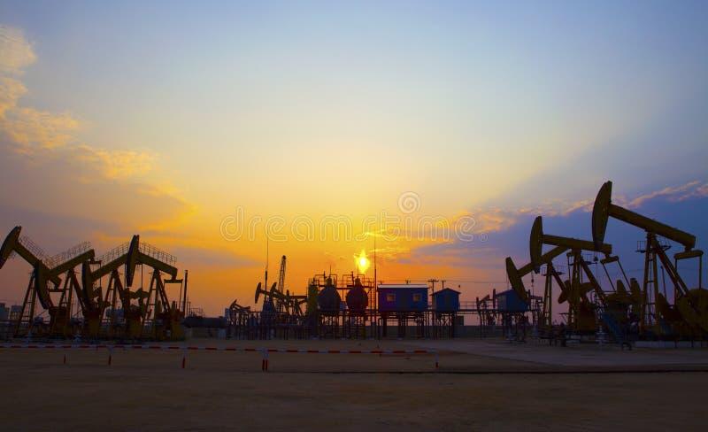 Bomba de aceite en puesta del sol anaranjada imagen de archivo