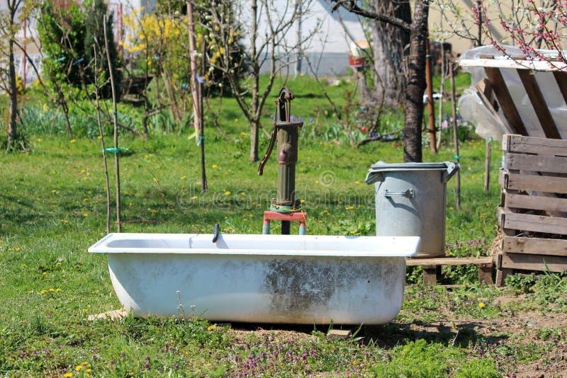 Bomba de agua aherrumbrada vieja retra de la mano del vintage con la bañera usada como tanque de agua en el jardín urbano local r fotos de archivo libres de regalías