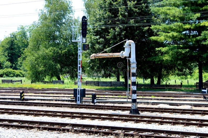 Bomba de agua blanca del metal viejo y negra ferroviaria al lado de pistas ferroviarias y del semáforo imágenes de archivo libres de regalías