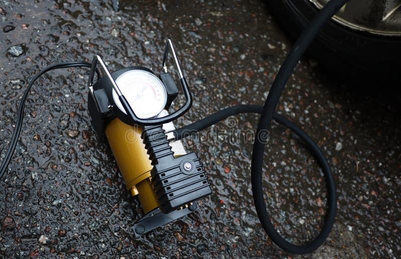 Bomba del coche El compresor automático del coche le ayudará a bombear el aire no sólo en las ruedas de su coche, pero también a  imagen de archivo libre de regalías