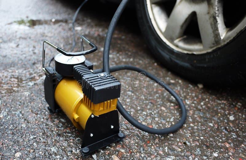 Bomba del coche El compresor automático del coche le ayudará a bombear el aire no sólo en las ruedas de su coche, pero también a  imagenes de archivo