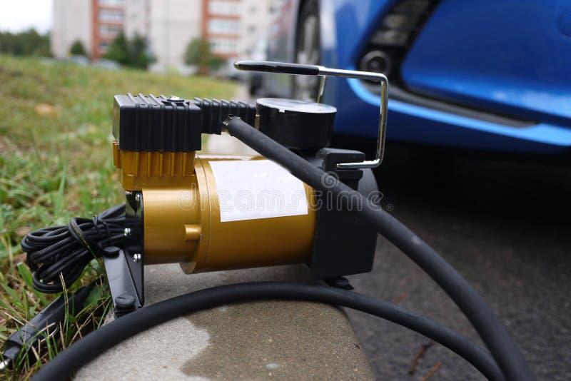 Bomba del coche El compresor automático del coche le ayudará a bombear el aire no sólo en las ruedas de su coche, pero también a  imagen de archivo