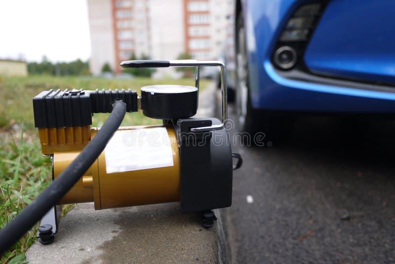 Bomba del coche El compresor automático del coche le ayudará a bombear el aire no sólo en las ruedas de su coche, pero también a  fotografía de archivo