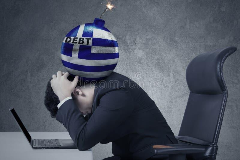Bomba del debito con una bandiera della Grecia sulla testa dell'uomo fotografia stock