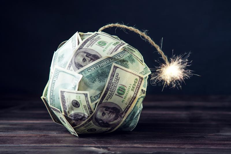 Bomba delle banconote in dollari dei soldi cento con uno stoppino bruciante Poco tempo prima dell'esplosione Concetto del crisi f immagini stock