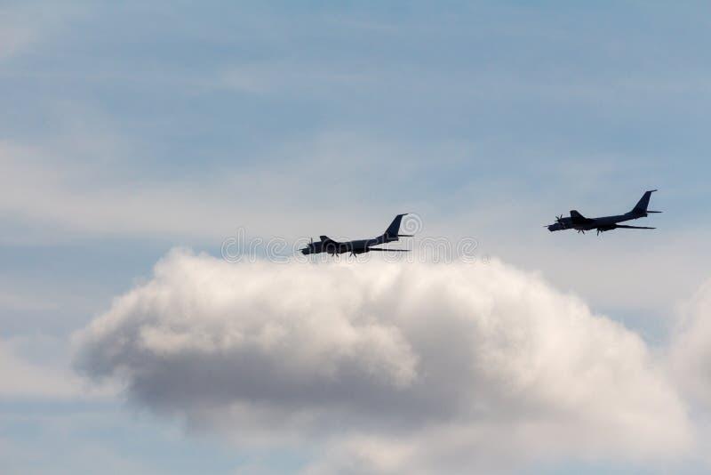 Bombardeiros estratégicos pretos do russo Tu-95 do voo das silhuetas contra o nome do relatório da OTAN do céu: 'Urso imagem de stock
