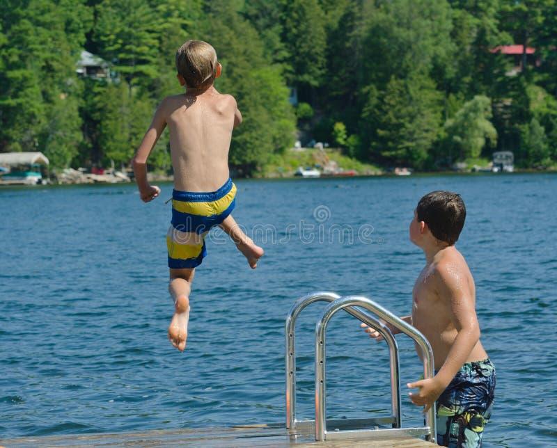Bombardement de piqué de garçon outre de dock dans le lac image libre de droits